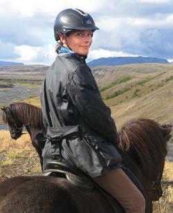 Islandsrejser arrangerer din rejse til Island. Her er Mette Viberg fra ISLANDSREJSER siddende på en islands hest i Island.